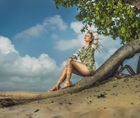 Stock Photo Pretty woman sitting on dry trunk