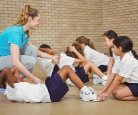 Student doing sit-ups in physical education class Stock Photo