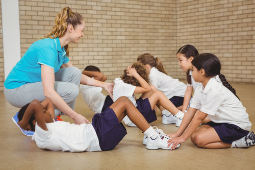 Student doing sit ups in physical education class Stock Photo