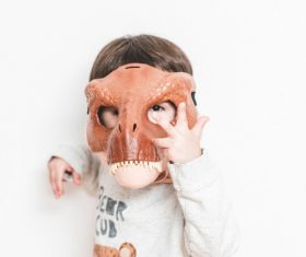Wearing dinosaur mask for children Stock Photo
