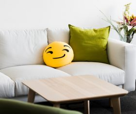 White Couch with Funny Emoji Pillow Stock Photo