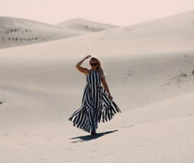 Woman walking in the desert Stock Photo