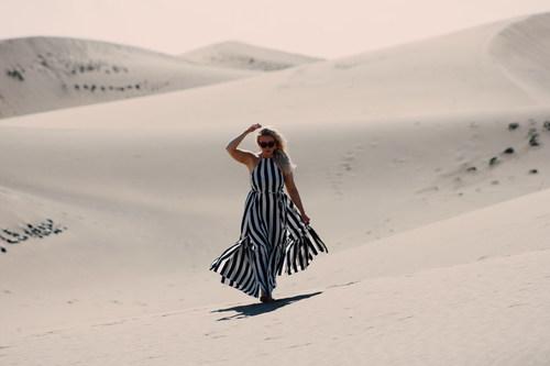 Woman walking in the desert Stock Photo