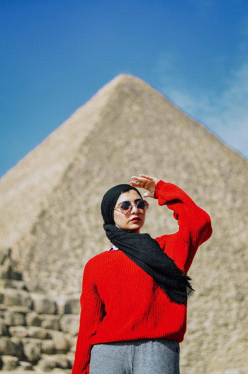 Woman with pyramid behind her Stock Photo