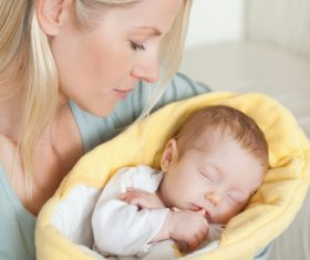 Young mother holding her sleeping baby Stock Photo 01