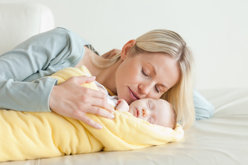 Young mother holding her sleeping baby Stock Photo 06