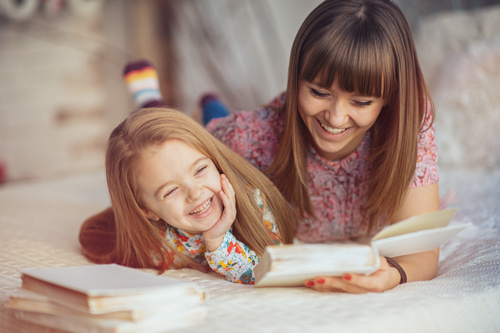 Young mother reads fairy tale book to daughter Stock Photo 01