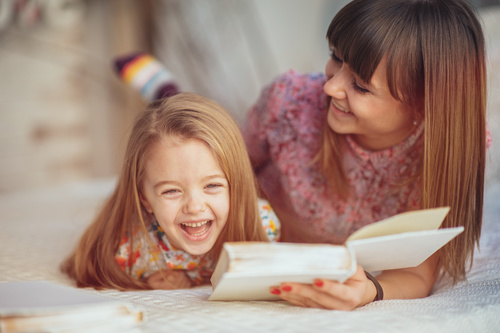 Young mother reads fairy tale book to daughter Stock Photo 02