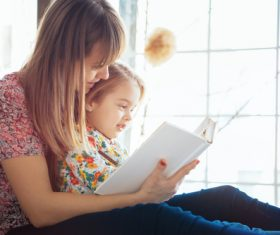 Young mother reads fairy tale book to daughter Stock Photo 03