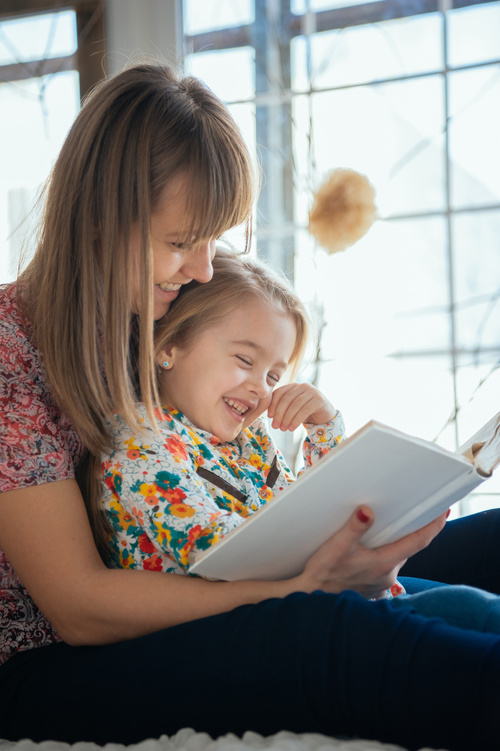 Young mother reads fairy tale book to daughter Stock Photo 04