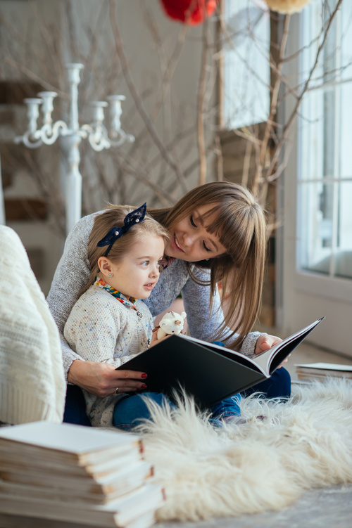 Young mother reads fairy tale book to daughter Stock Photo 05