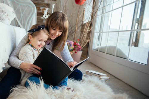 Young mother reads fairy tale book to daughter Stock Photo 06
