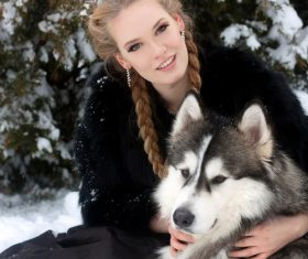 Young woman with wolf dog in snow Stock Photo 01