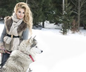 Young woman with wolf dog in snow Stock Photo 03