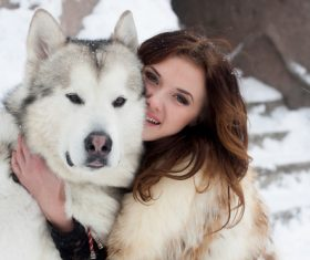 Young woman with wolf dog in snow Stock Photo 04