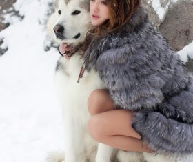 Young woman with wolf dog in snow Stock Photo 05