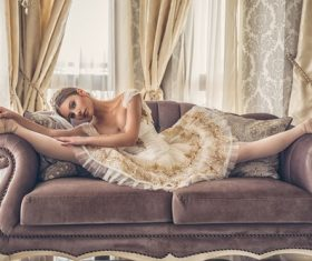 Ballet girl doing splits on the couch Stock Photo