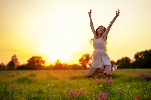 Beautiful woman jumping up in mid air Stock Photo
