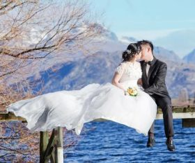 Bride groom sitting on the wooden bridge Stock Photo