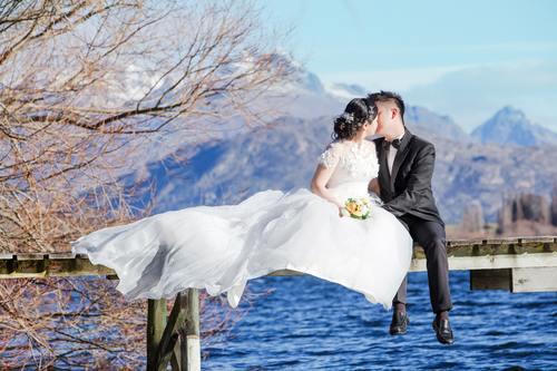 Bride groom sitting on the wooden bridge Stock Photo