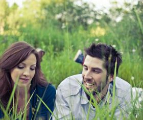 Couple lying on the grass talking Stock Photo
