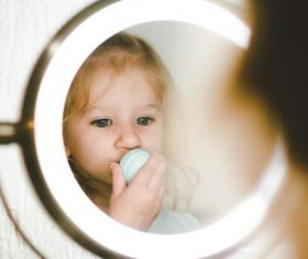 Cute blond little girl looking in the mirror Stock Photo 01