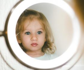 Cute blond little girl looking in the mirror Stock Photo 02