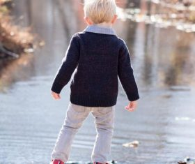 Little boy looking at the fallen leaves in the river Stock Photo
