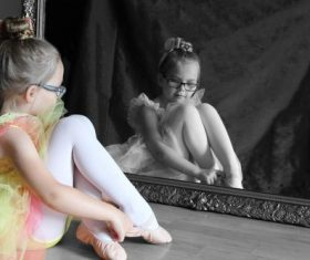 Little girl sitting in front of the mirror wearing dance shoes Stock Photo