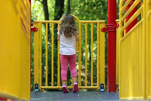 Little girl standing on the slide Stock Photo