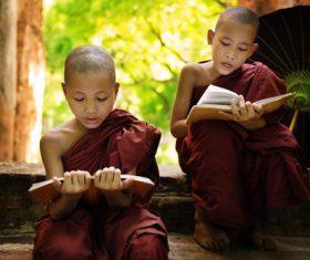 Little monk reading book Stock Photo