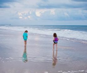 Little sisters walking by the sea Stock Photo