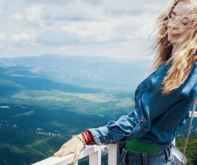 Long-haired beauty next to the guardrail on the top of the mountain Stock Photo