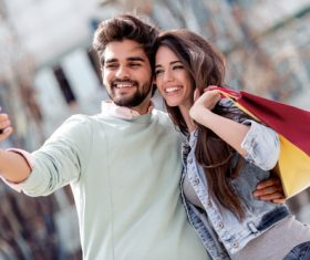 Portrait of a couple with shopping bags in city Stock Photo 04