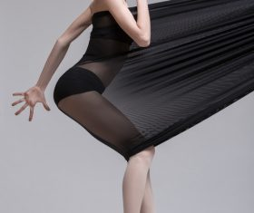 Slim dancer plays with black mesh fabric in the studio Stock Photo 01