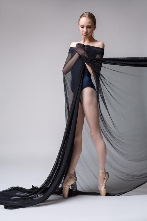 Slim dancer plays with black mesh fabric in the studio Stock Photo 04