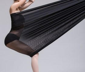 Slim dancer plays with black mesh fabric in the studio Stock Photo 05