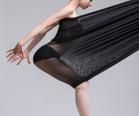 Slim dancer plays with black mesh fabric in the studio Stock Photo 07