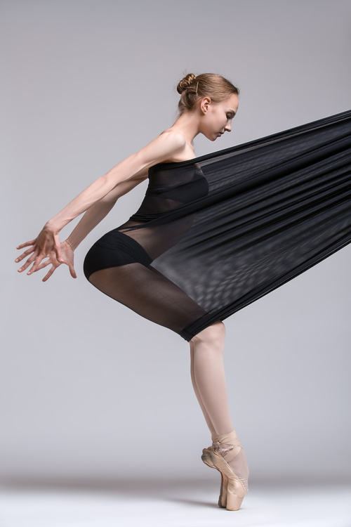 Slim dancer plays with black mesh fabric in the studio Stock Photo 07