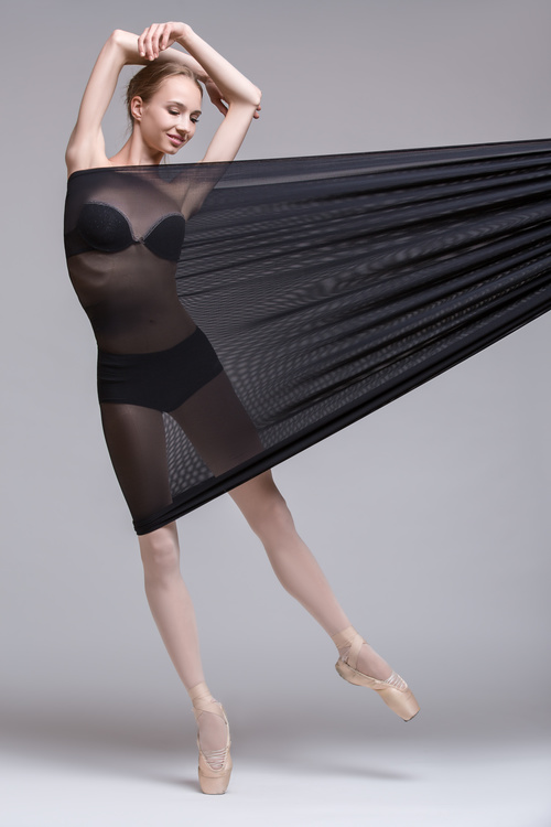 Slim dancer plays with black mesh fabric in the studio Stock Photo 08