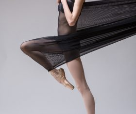 Slim dancer plays with black mesh fabric in the studio Stock Photo 09