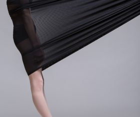 Slim dancer plays with black mesh fabric in the studio Stock Photo 11
