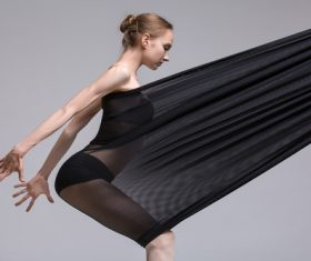 Slim dancer plays with black mesh fabric in the studio Stock Photo 12