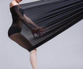 Slim dancer plays with black mesh fabric in the studio Stock Photo 13