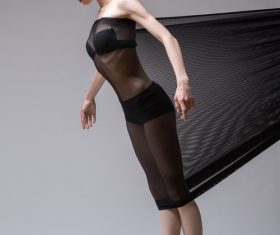 Slim dancer plays with black mesh fabric in the studio Stock Photo 14