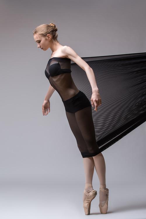 Slim dancer plays with black mesh fabric in the studio Stock Photo 14