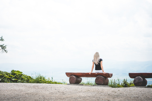 Woman Sitting on a Bench look at the scenery Stock Photo