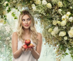 Woman holding apple with flower background Stock Photo
