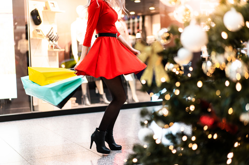 Woman in Red Dress Enjoying Christmas Shopping Stock Photo