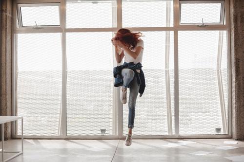 Woman jumping indoors Stock Photo